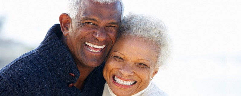 smiling mature couple who had porcelain veneers to repair chipped teeth